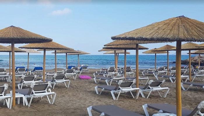 Фото пляжа Гувес с зонтиками и шезлонгами на острове Крит
